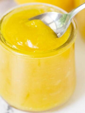 vegan lemon curd in glass jar with spoon