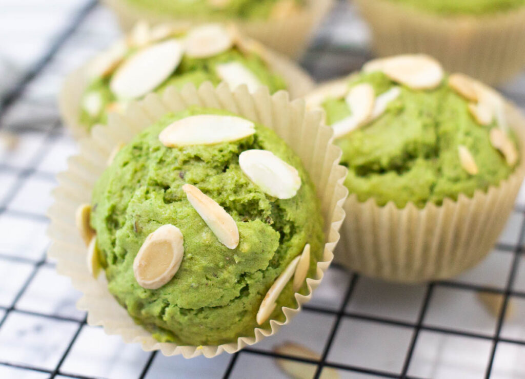 baked matcha muffins topped with sliced almonds