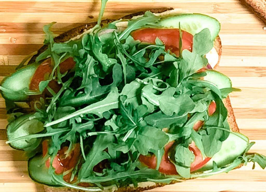 bread topped with cucumber, tomato, and arugula