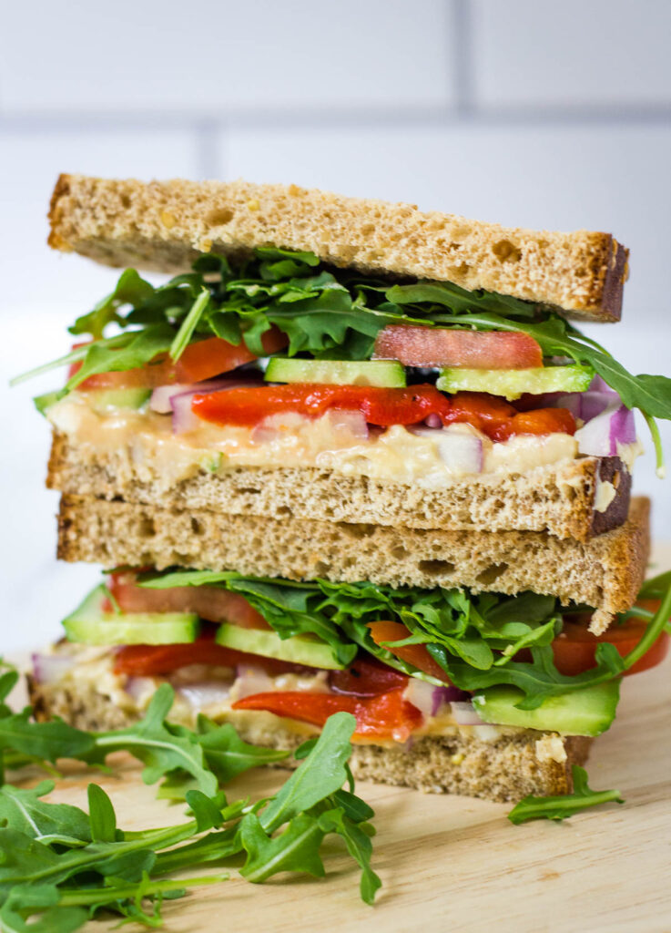veggie sandwich with arugula, tomato, cucumber, red onion, hummus, and red pepper on whole wheat