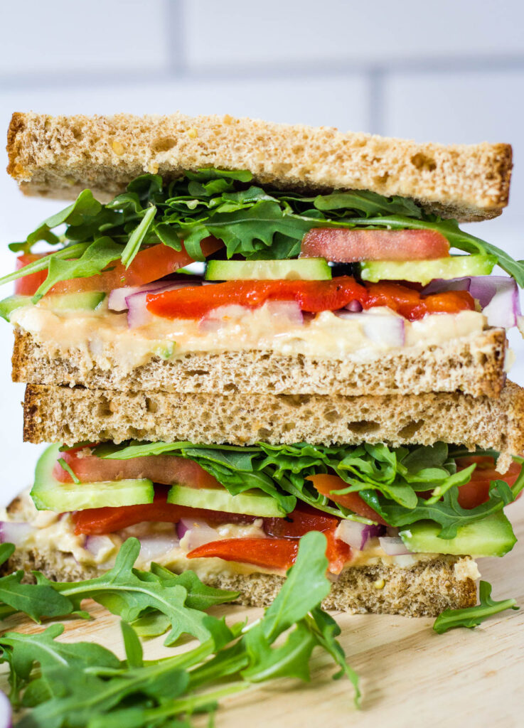 Mediterranean veggie sandwich halves stacked on top of one another.