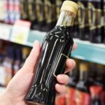hand holding bottle of soy sauce in grocery store