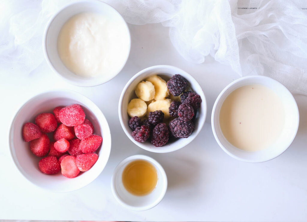 Ingredients for strawberry banana smoothie: frozen strawberries, frozen blackberries, frozen banana, almond milk, non-dairy yogurt, and maple syrup