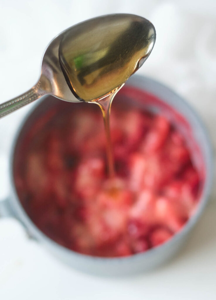 Maple syrup on a spoon poured into pot with simmering strawberries.