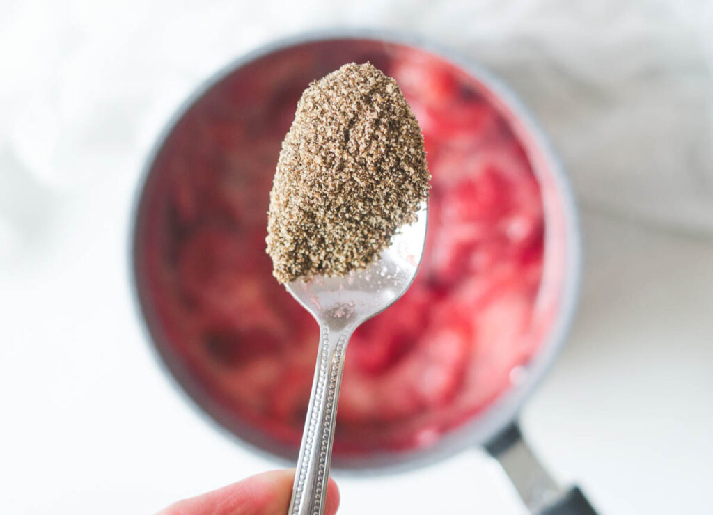 Ground chia on a spoon added to pot of simmering strawberries.
