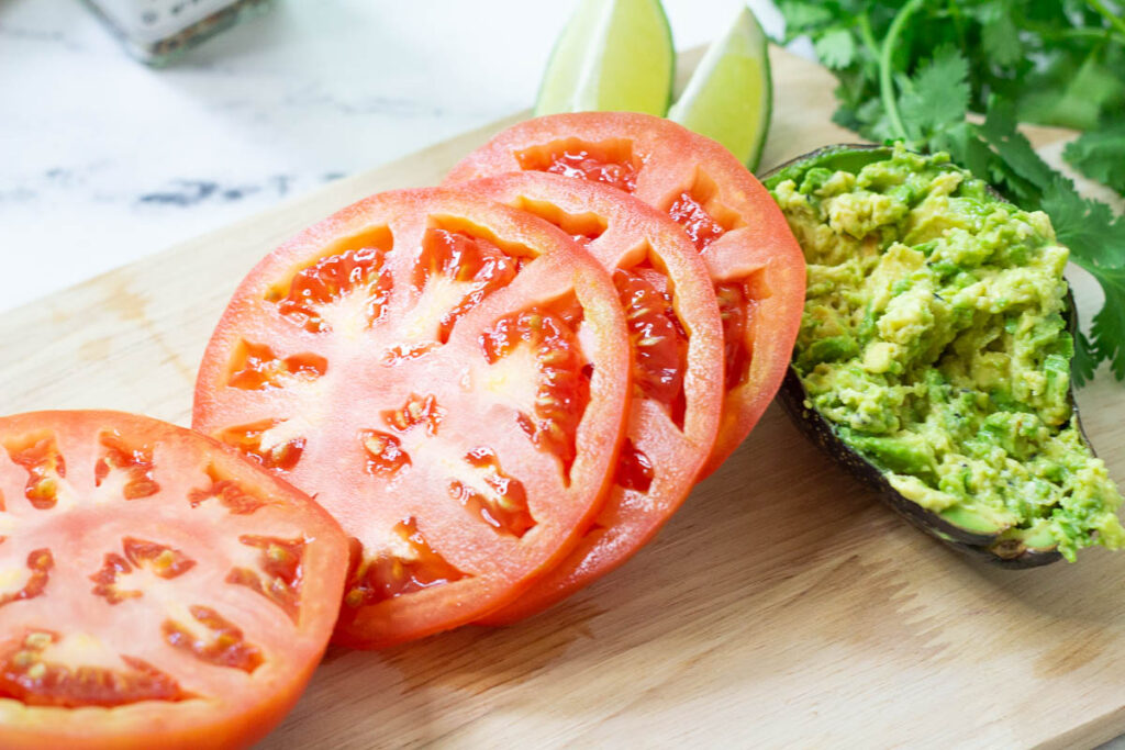 large slices of tomato next to an avocado skin filled with mashed avocado