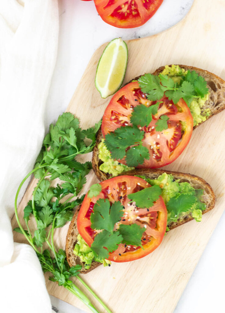two tomato avocado toast slices served on cutting board, next to a garnish of cilantro, and a wedge of lime