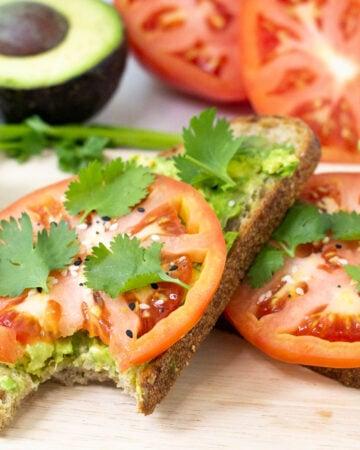 two slices of tomato avocado toast with bite taken out
