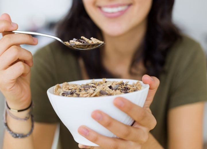 smiling woman lifting a spoon of vegan cereal from a white bowl