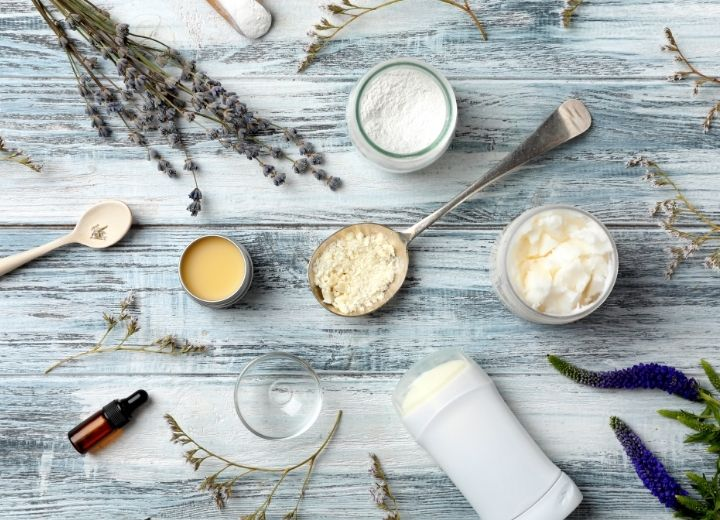 deodorant, powders, cream, essential oils, and spoons on white wash table with wild flowers
