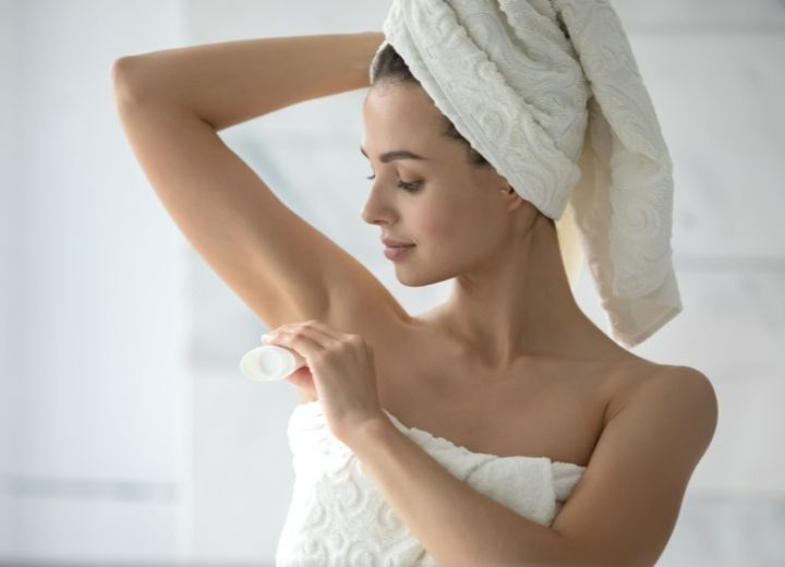 woman wrapped in towel putting on deodorant