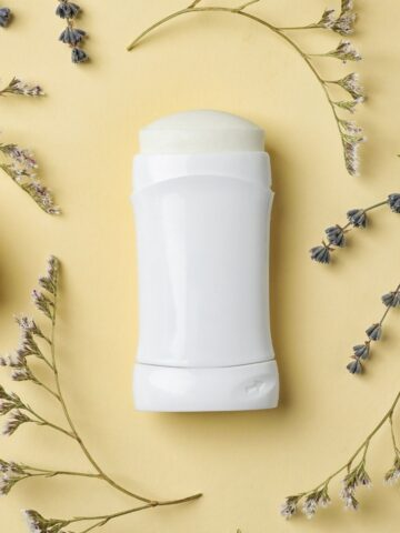 roll on vegan deodorant on beige background surrounded by wild flowers