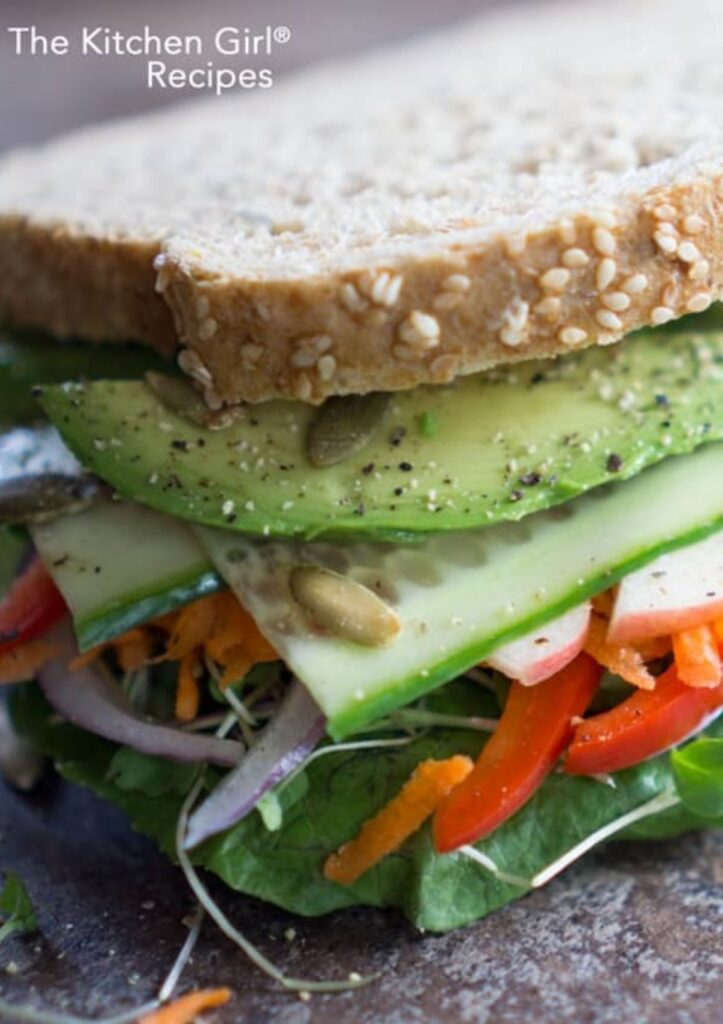 layers of vegetables like avocado, cucumber carrot, red pepper, sprouts, and greens on whole grain bread