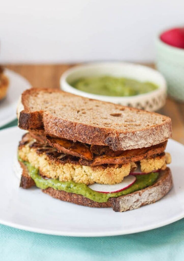 roasted cauliflower on whole wheat bread served on white plate