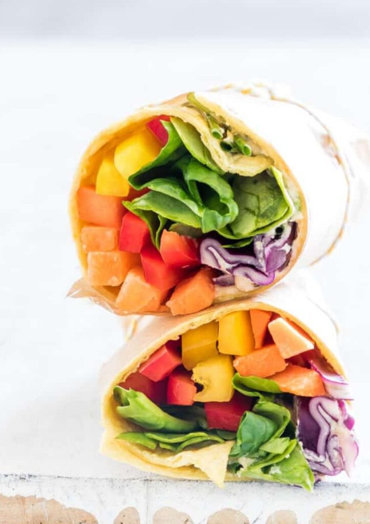 Rainbow veggie hummus wrap sliced in half and stacked