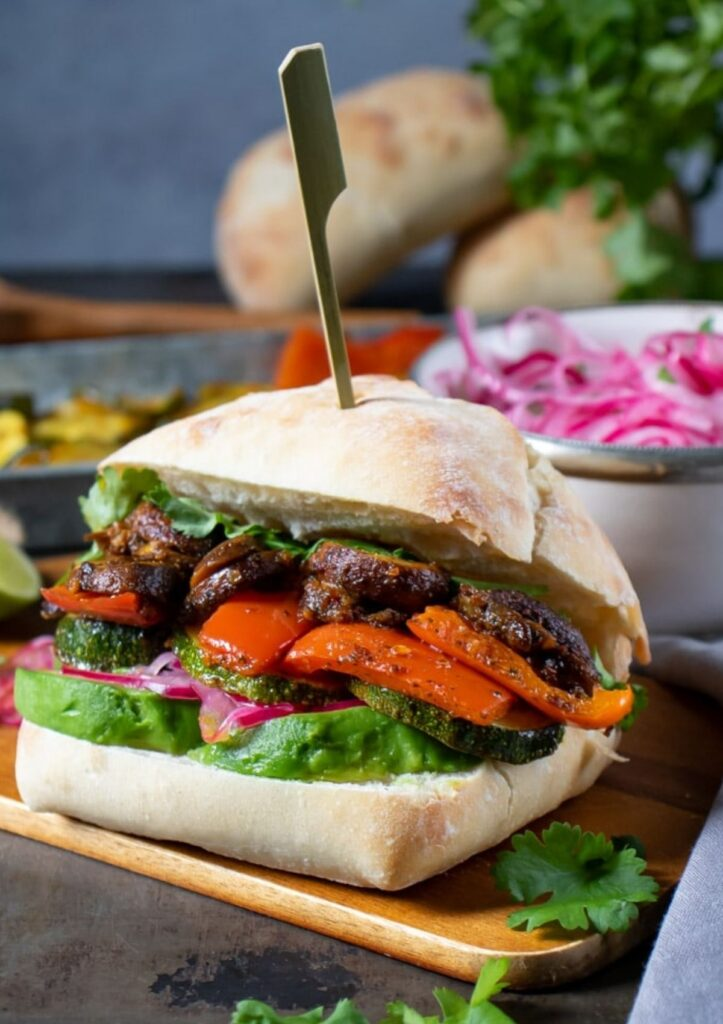 Peruvian veggie sandwich with roasted vegetables served on wood serving tray