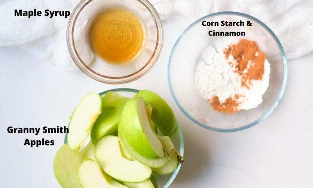 Bowl of sliced granny smith apples, bowl of corn starch and cinnamon, bowl of maple syrup.