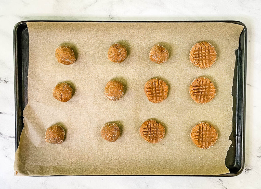 Raw cookie balls on baking sheet, with some pressed into a crisscross pattern.
