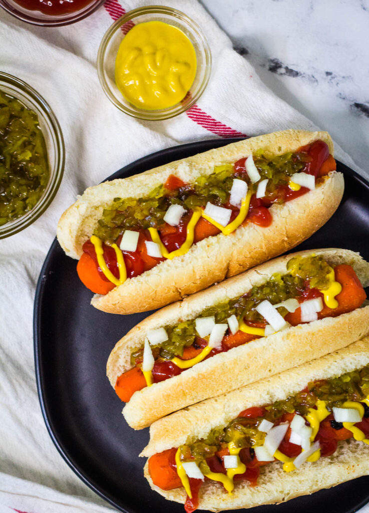 Three carrot hot dogs on black plate topped with relish, onion, mustard, and ketchup.