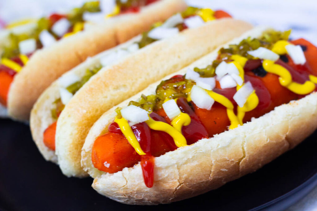 Vegan carrot hot dogs on black plate topped with onion, relish, mustard, and ketchup.