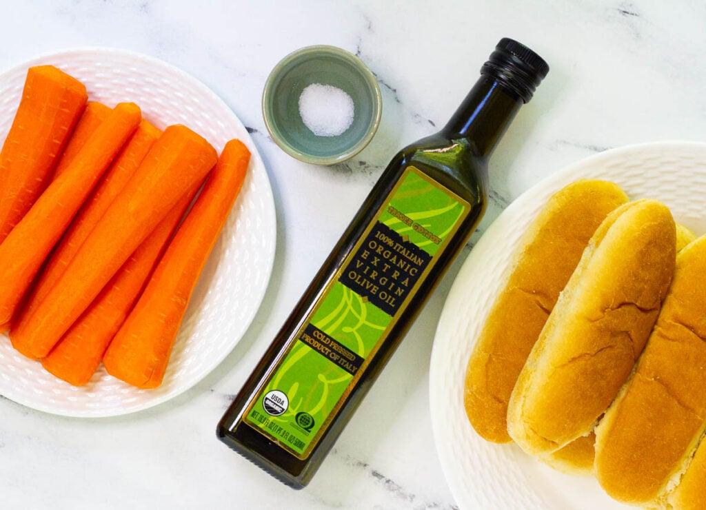 Trimmed carrots, salt, olive oil, and hot dog buns.