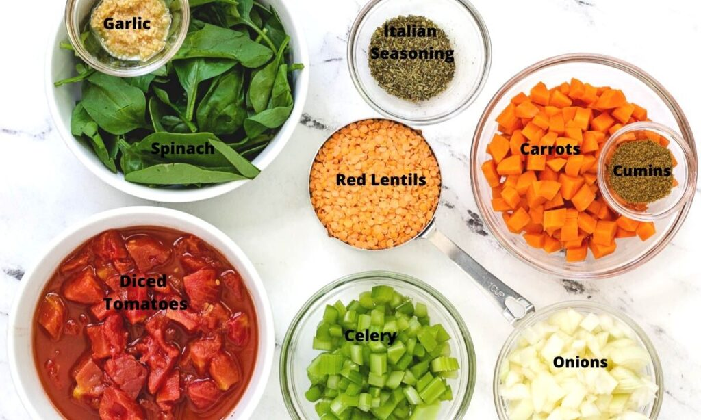 Ingredients for lentil soup: garlic, spinach, Italian Seasoning, Cumin, carrots, red lentils, diced tomatoes, celery, and onions.