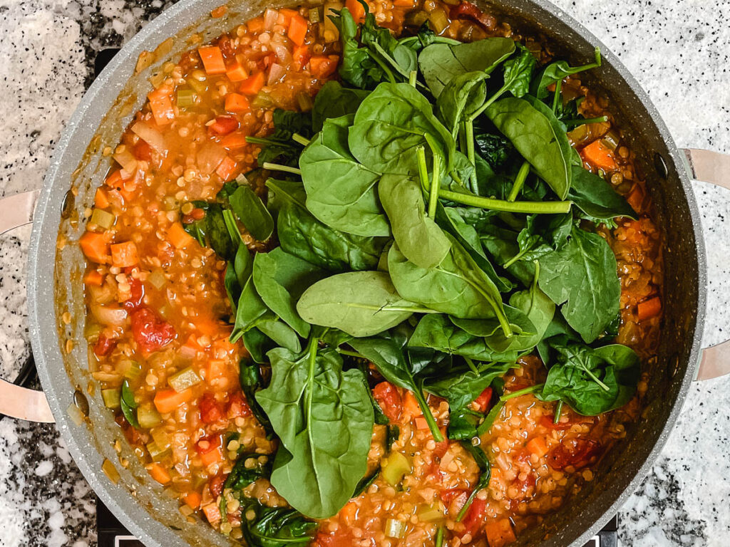 Red lentil soup in pot topped with leaf spinach.