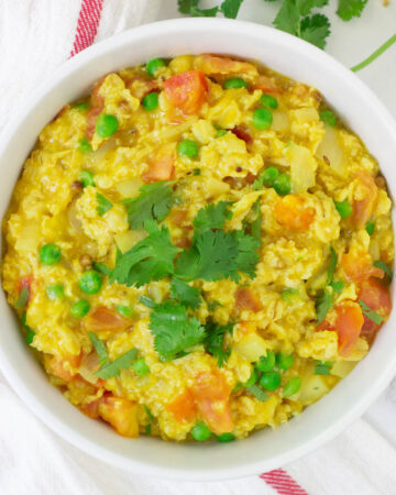 bowl of savory masala oats topped with cilantro leaves