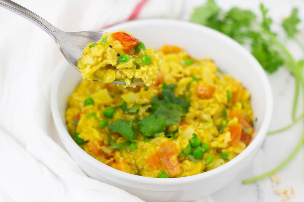 Spoon of oats helps over bowl of savory curry oats with peas and tomatoes.