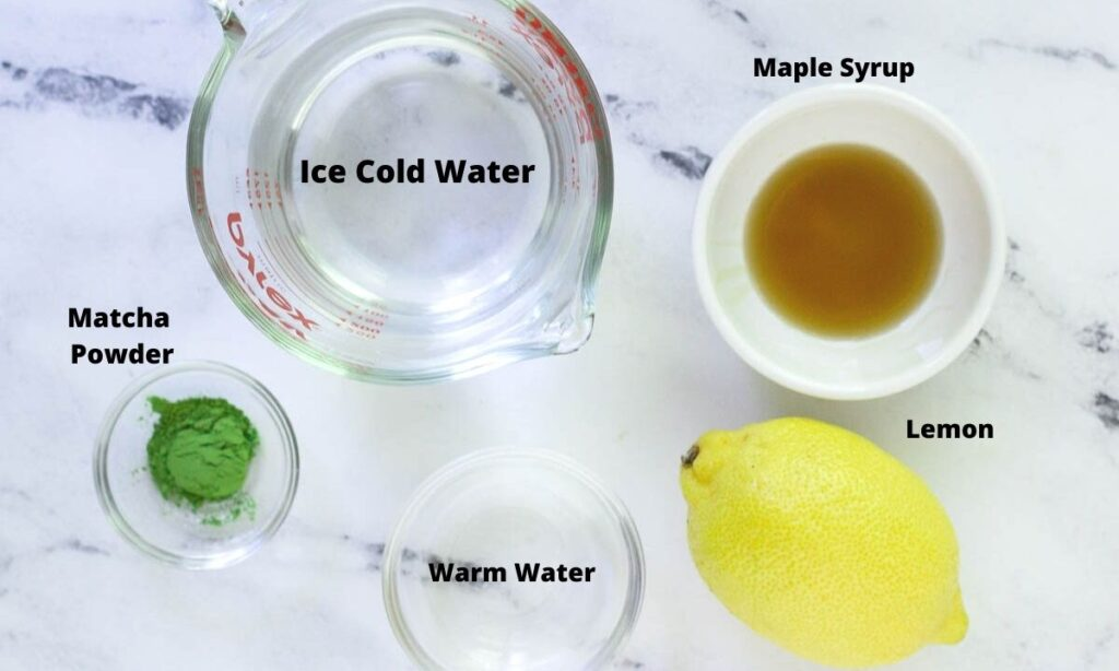 Ice cold water, maple syrup, matcha powder, lemon, and warm water on countertop.