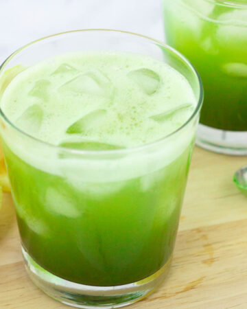 Matcha lemonade in glass with ice.