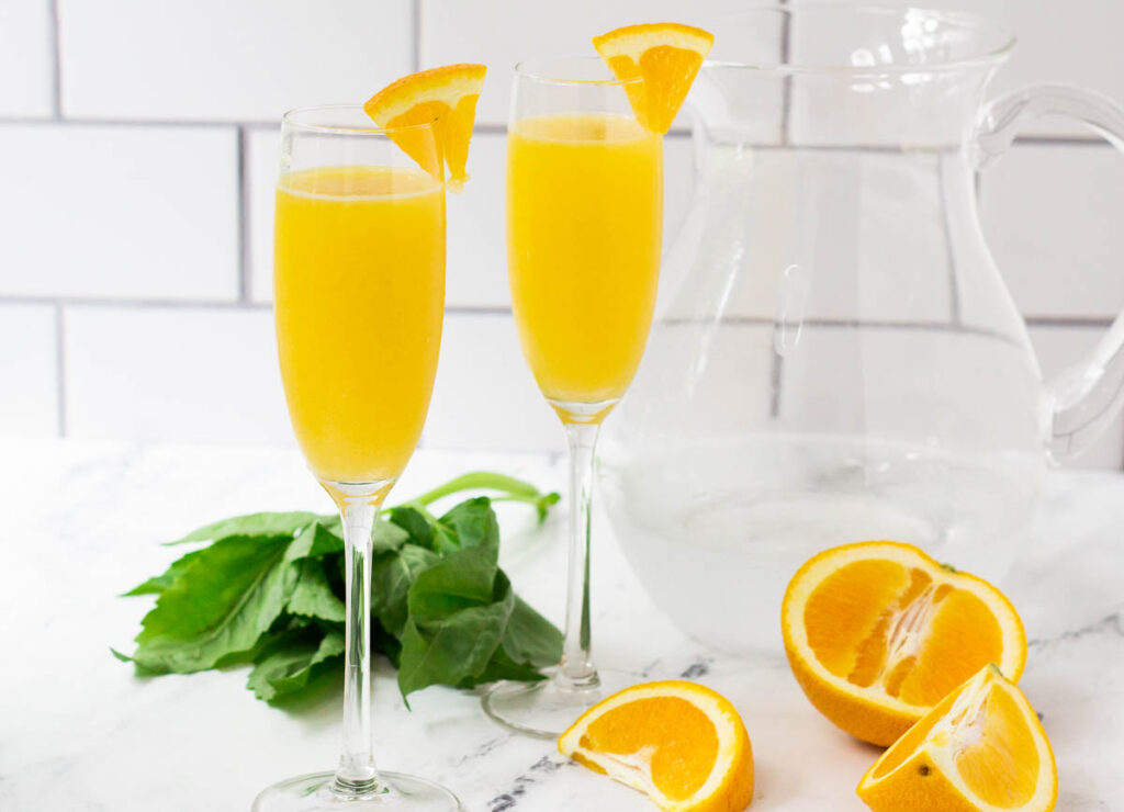 Two mimosas beside a bunch of basil, sliced oranges, and a pitcher of sparkling water.