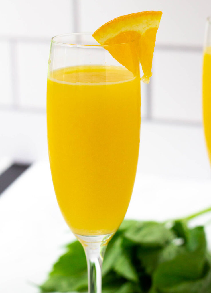 Champagne flute filled with a orange juice and sparkling water, and garnished with a wedge of orange.