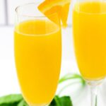 Two mimosas with a wedge of orange.