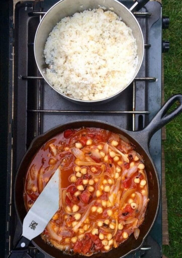 Chickpea curry and rice in pots on outdoor stove.