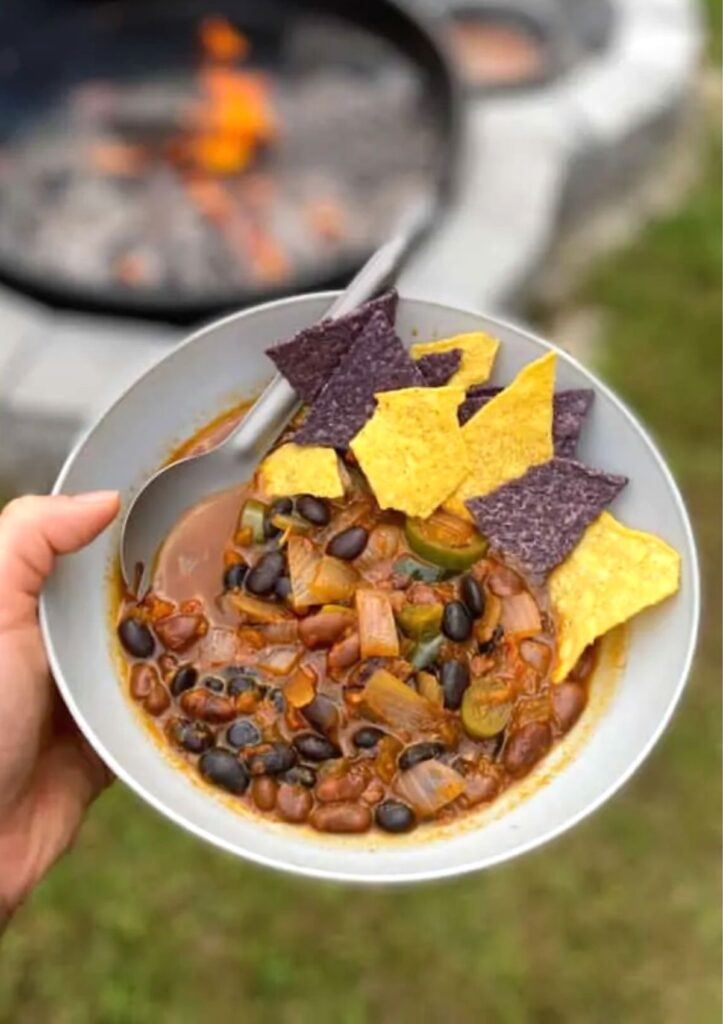 Hand holding a bean chili bowl with chips near a campfire.
