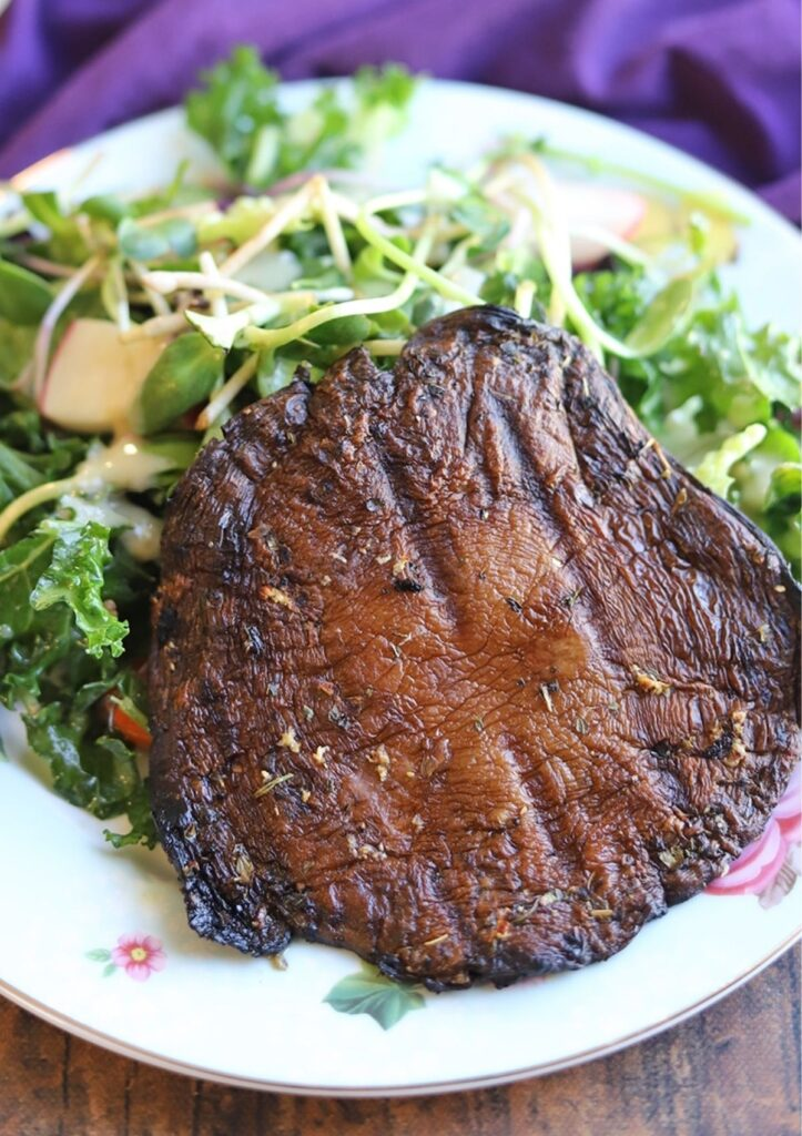 Grilled portobello steaks served with salad on white plate.