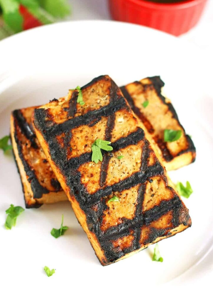 Tofu steaks with grill marks on white plate.