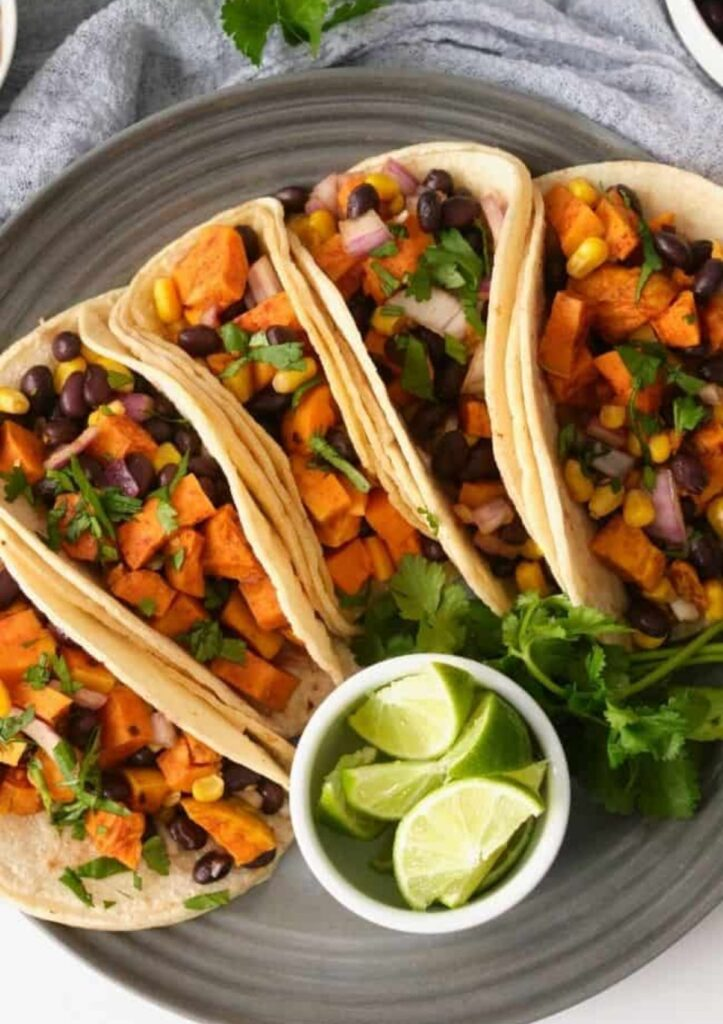 Black bean and sweet potato tacos with wedges of lime.