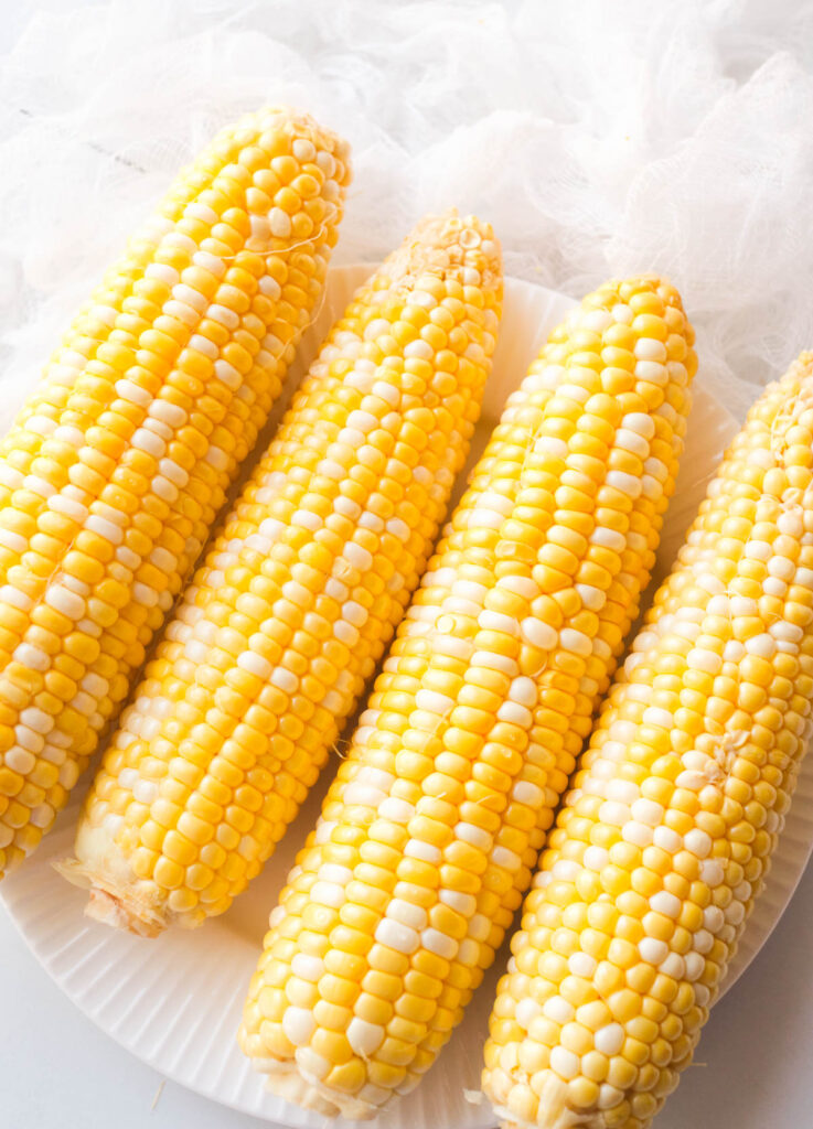 Four ears of corn shucked and cleaned on a white plate.