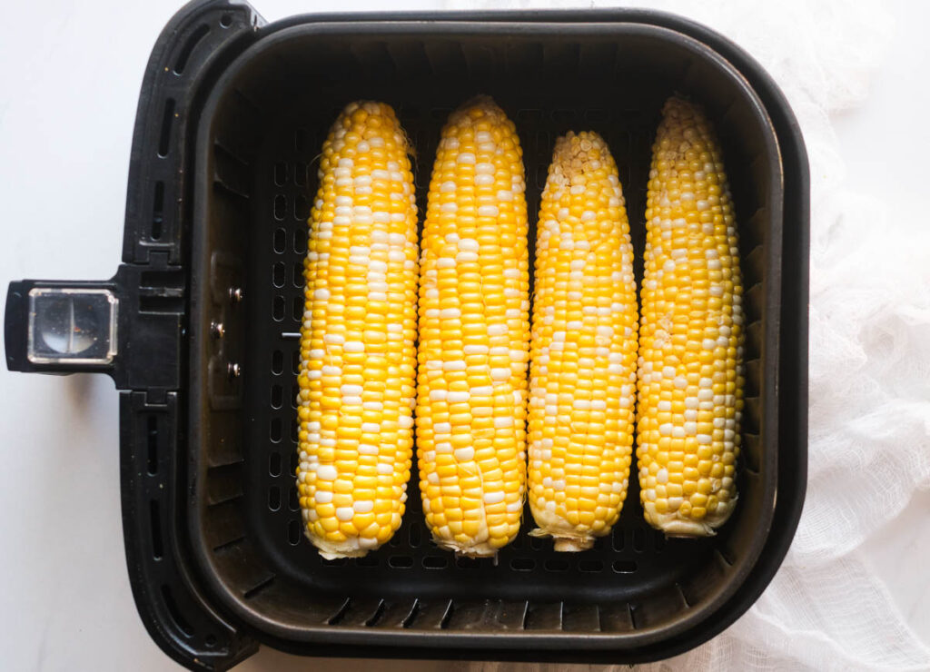 Four ears of corn in a single layer at the bottom of an air fryer basket.