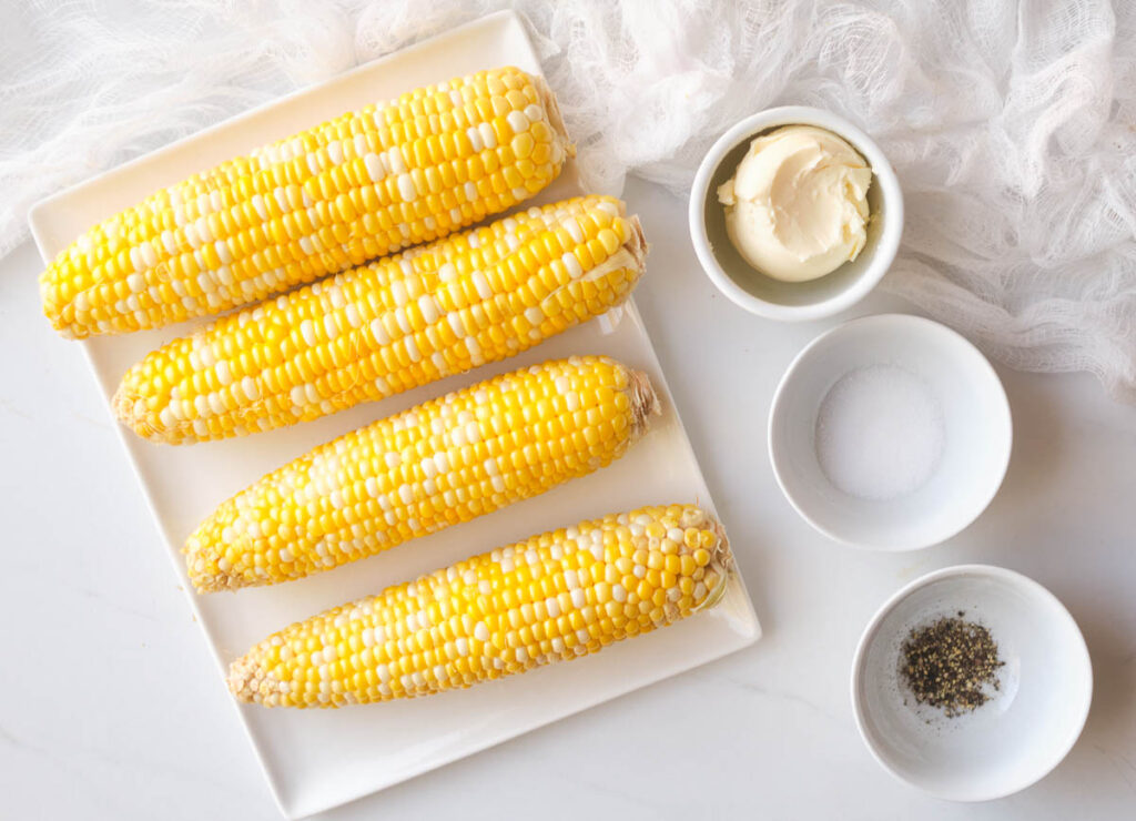Four ears of corn on a rectangular plate, next to small bowl of butter, salt, and pepper.
