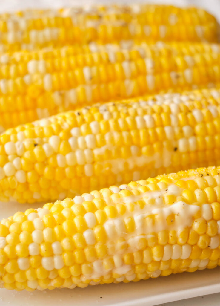 Close up of cooked corn lined on a plate topped with melted butter, salt, and pepper.