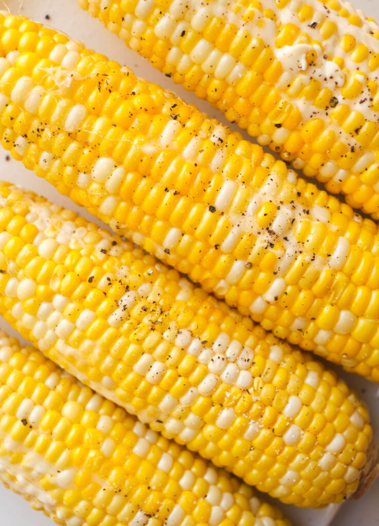 Cooked corn on the cob topped with melted butter, salt, and pepper.