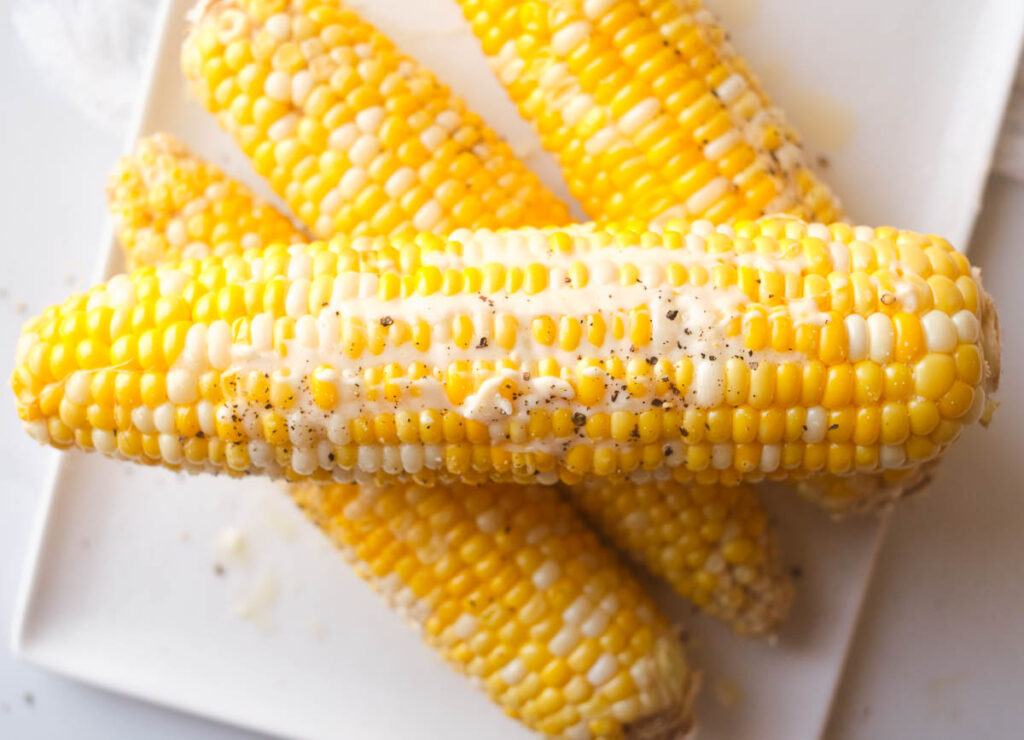 Four cooked ears of corn stacked on a white plate topped with butter, salt, and pepper.