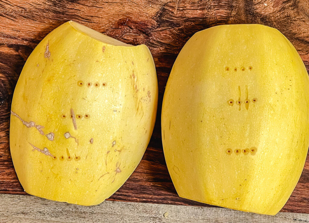 Spaghetti squash halves with skin facing up, and fork holes added.