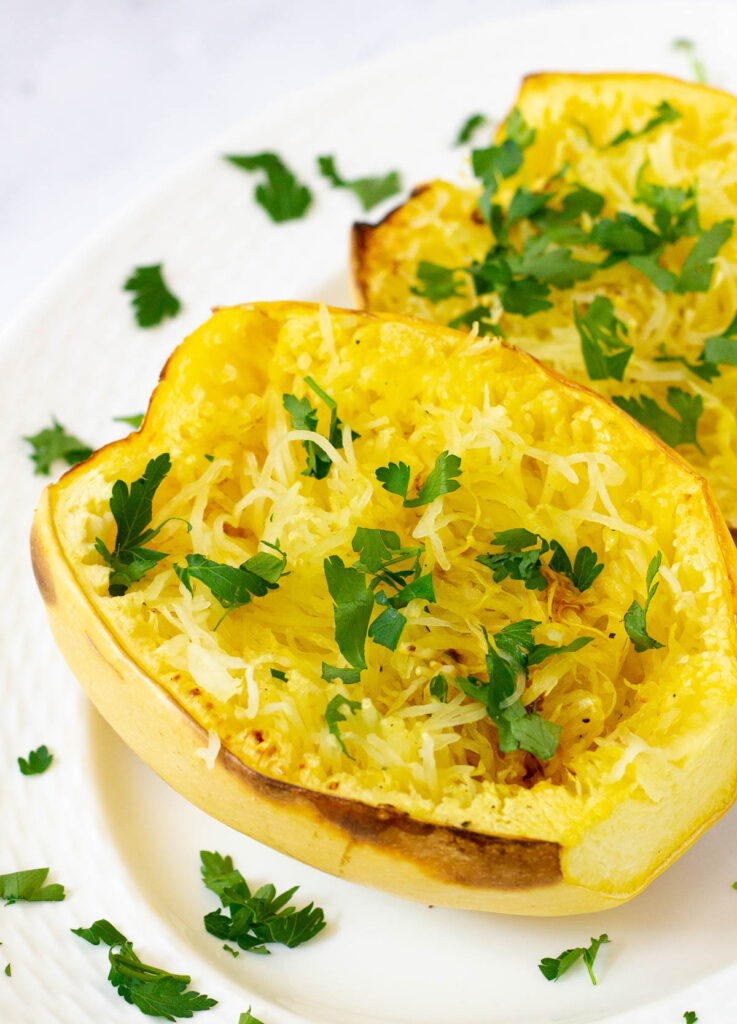 Roasted spaghetti squash halves on white plate topped with chopped parsley.