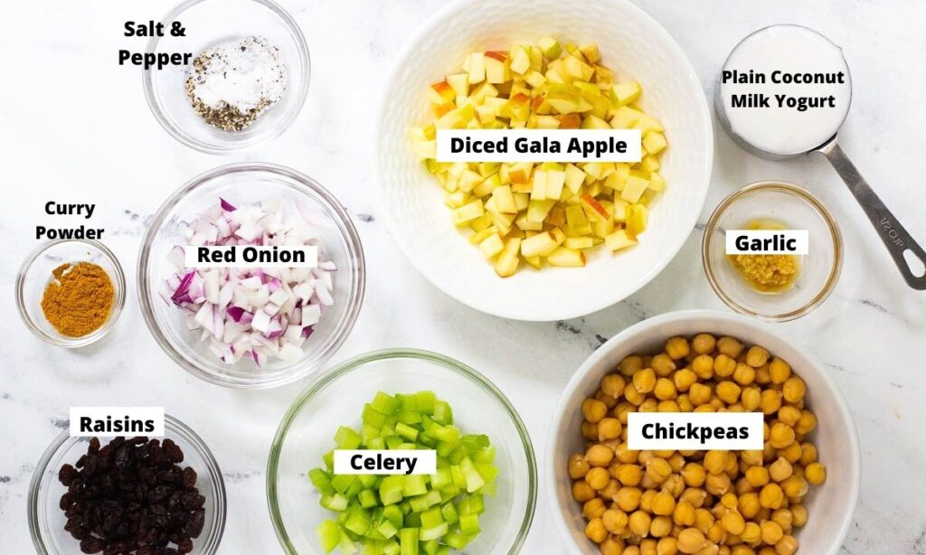Ingredients for chickpea salad in bowls: salt and pepper, red onion, curry powder, raisins, celery, chickpeas, garlic, diced gala apple, and plain coconut milk yogurt.