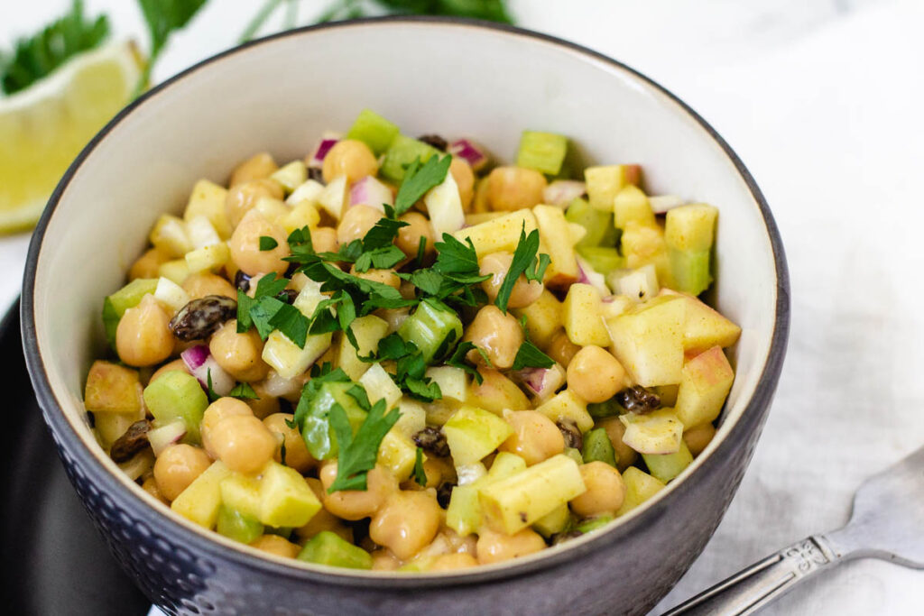 Chickpea salad in bowl topped with parsley.