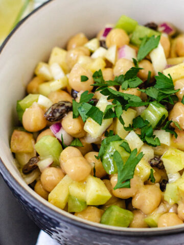 Chickpea curry salad in bowl topped with parsley.